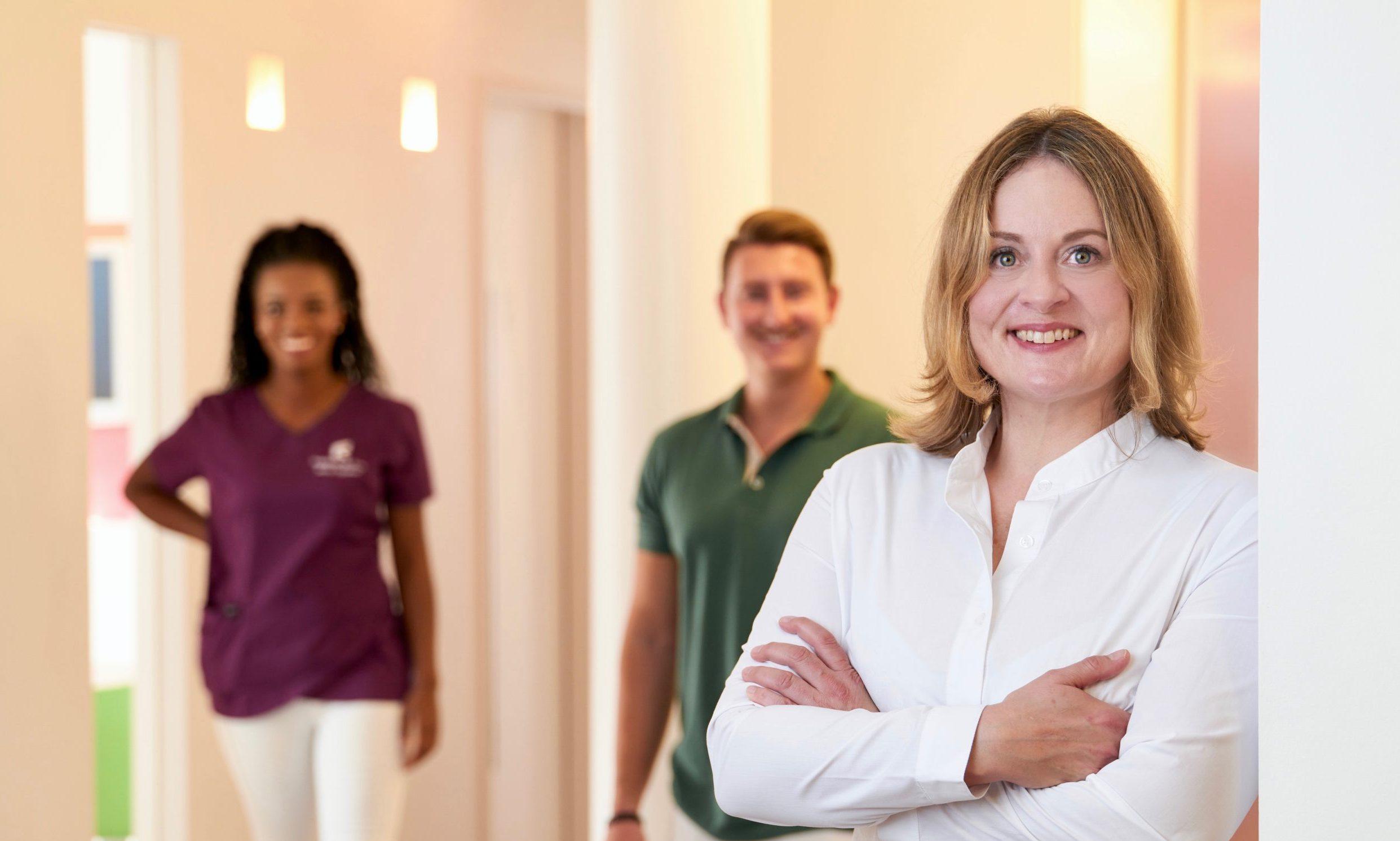 Dr. Friederike Krop mit verschränkten Armen und Lächeln in Ihrer Praxis