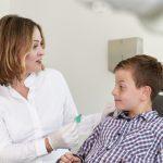 Behandlungssituation mit Kind, Einsetzen einer herausnehmbaren Zahnspange